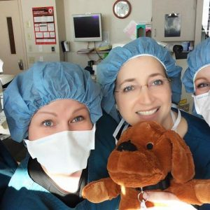 Doctor Graham and staff prepared for surgery hold a stuffed dog.