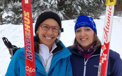 Dr. Relf and Dr. Graham pose with their skis on a snowy hill.