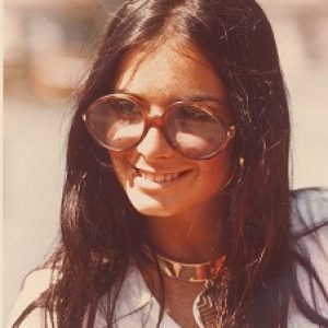 A woman in large round sunglasses that were common in the 1970s.