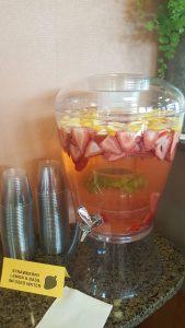 A beverage dispenser full of lemons, strawberries and mint water.