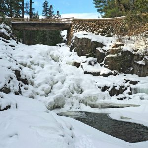 A frozen waterfall under a snow covered bridge.