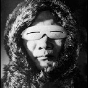 An image of an Eskimo with a pair of primitive sunglasses.