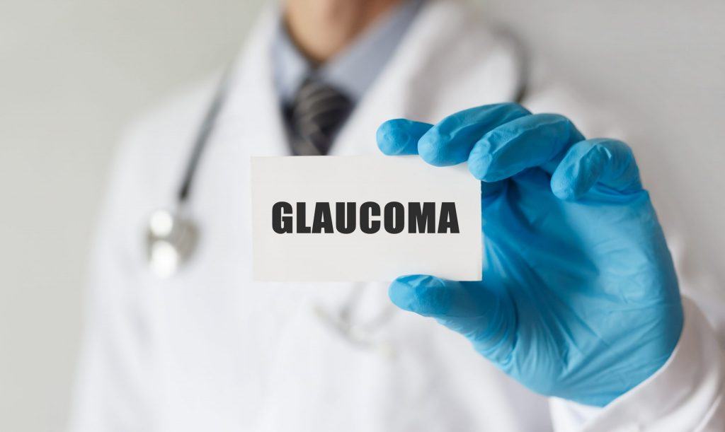 An eye doctor holding a card with text, GLAUCOMA.
