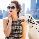 A woman models Bon Vivant prescription sunglasses while sitting near the water with her dalmatian.