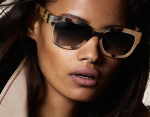 A woman models Burberry prescription Sunglasses that are available at Relf EyeCare.