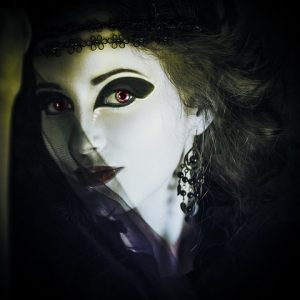 A woman with a white painted face and costume contact lenses.