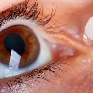 close up of eye drop being placed in brown eye