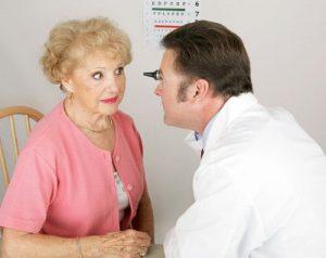 An eye doctor looks in the eye of a elderly woman.
