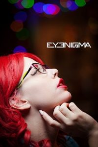 A woman with candy apple red hair models a pair of Eyenigma eye glasses.