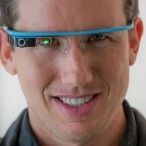 A man wearing a pair of blue Google Glass glasses.