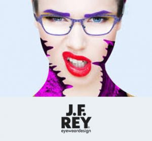 A woman models a sharp pair of bright purple eyeglasses, an abstract shirt, and a bright red lip.
