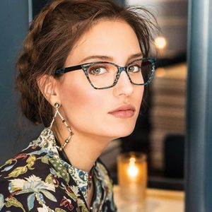 A woman models fashion eyeglasses available in Hermantown and Duluth at Relf EyeCare.
