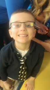 A little boy with glasses smiling.