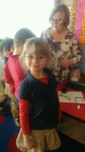 A little girl smiles wearing glasses.