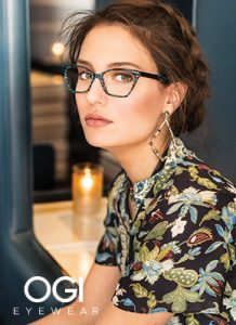 A woman in a floral shirt models a blue and tortoise shell OGI fashion eyewear frames.