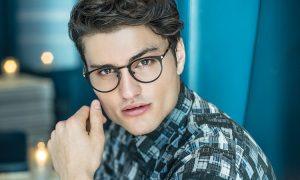 A man models black rimmed O.G.I. eye glasses frames.