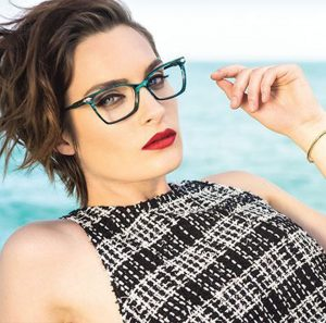 A woman models fashion eyewear available in Relf Optical.