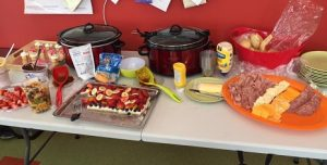 A picture of our potluck: fruit, cheesecakes, chili, meat and cheese, cupcakes and crockpots of goodies.