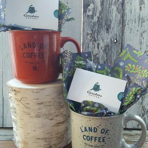 Two Caribou Coffee gift certificates and coffee mugs.